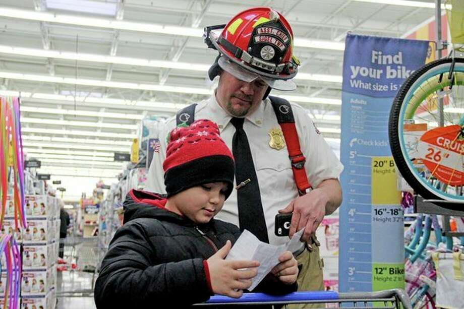Russel Lemanski (right) looks over Logun Kruse's Christmas shopping list during the Shop with a Hero event Wednesday afternoon at the Bad Axe Wal-Mart. The event saw the most children and heroes that it has ever had, as 105 children were able to shop for their families. (Mike Gallagher/Huron Daily Tribune)