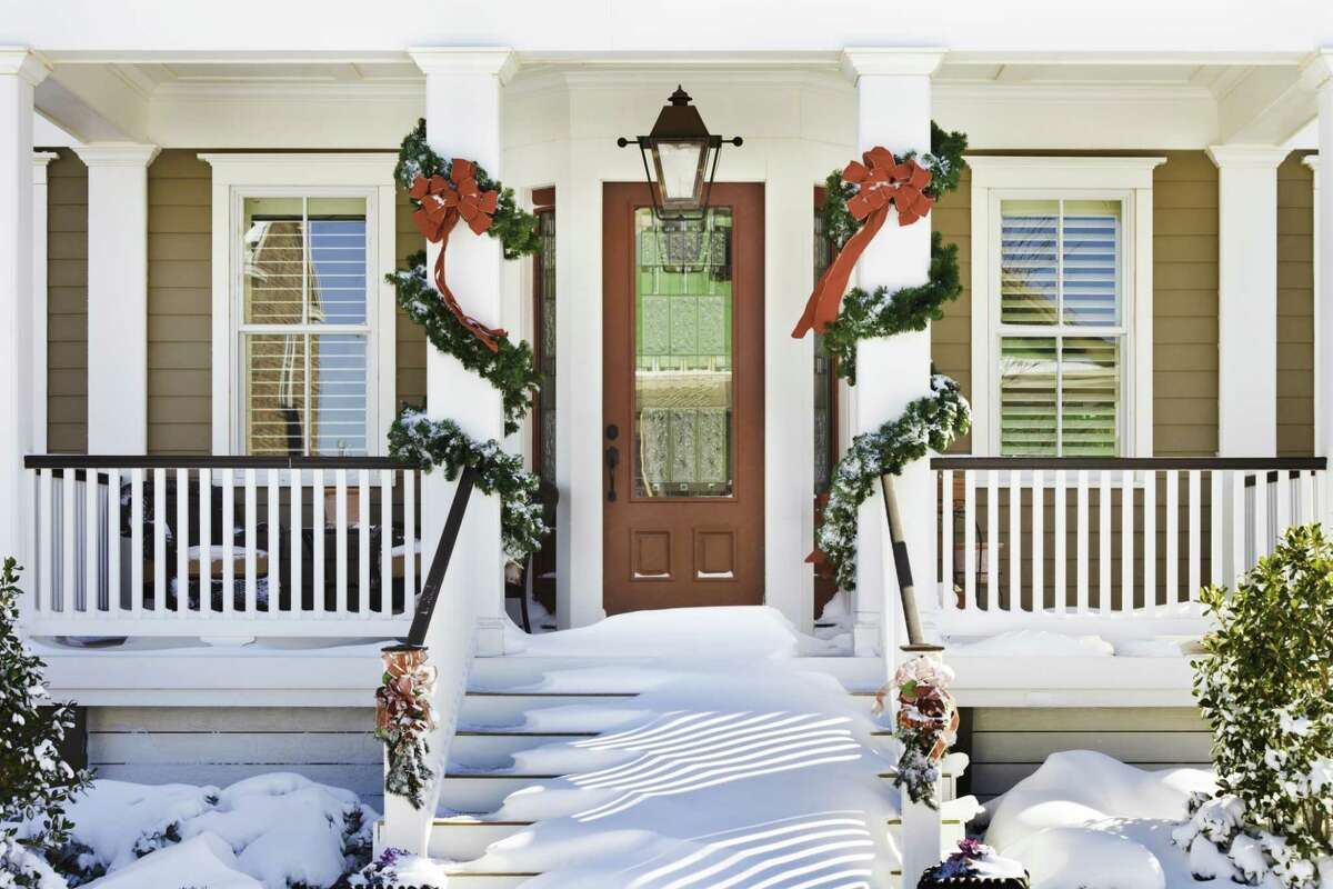 inviting doorway with snow on porch stairs and railing