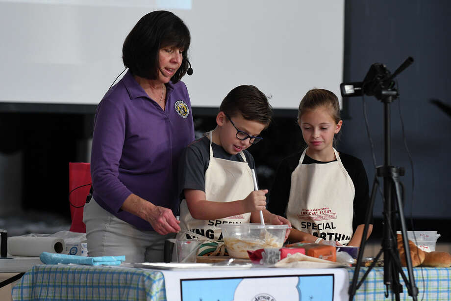 Wilson Murray, 9, center, and CC Cacchione, 10, right, both 4th graders, listen to instructions from Pam Jensen, left, of Alpine, UT., from King Arthur Flour's Bake for Good Program, as they mix the ingredients for making bread during their participation in a hands-on dough making and bread forming class for the entire KES 4th grade in the school cafetorium on Dec. 13, 2018. Photo: Jerry Baker, Contributor / Houston Chronicle