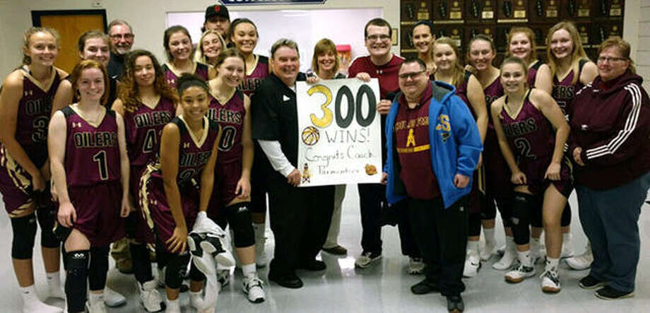 The EA-WR Oilers girls basketball team celebrates coach Joe Parmentier's 300th career victory as a basketball coach on Thursday night after EA-WR's victory in the Candy Cane Classic at Waterloo Gibault. Photo: Submitted Photo