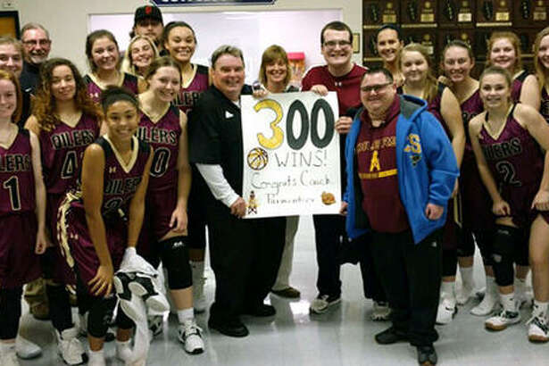 The EA-WR Oilers girls basketball team celebrates coach Joe Parmentier's 300th career victory as a basketball coach on Thursday night after EA-WR's victory in the Candy Cane Classic at Waterloo Gibault.
