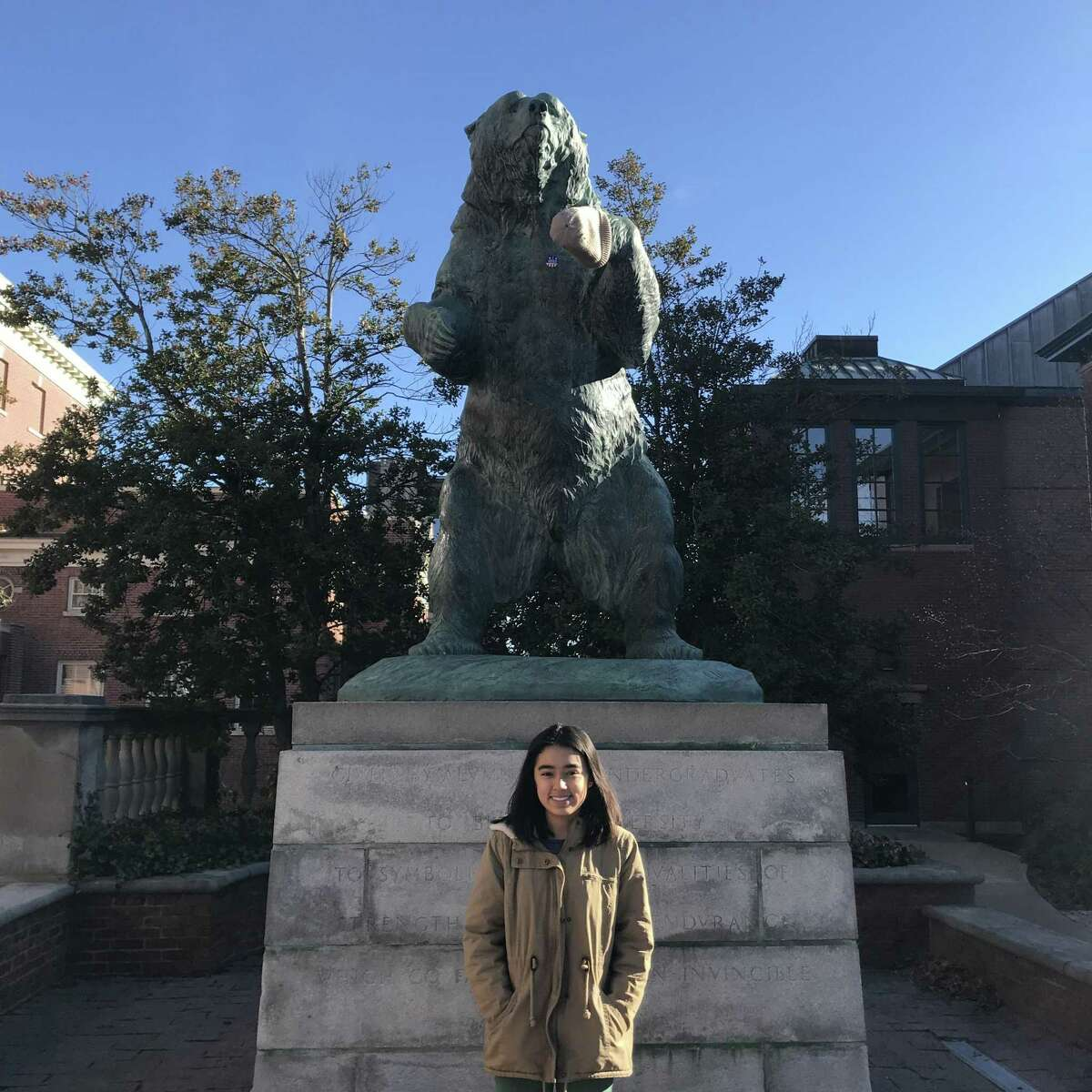 Teresa Conchas, who graduated earlier this year from Young Women's Leadership Academy as valedictorian, stands in front of a bronze statue of Bruno the bear on the main green at Brown University in Rhode Island.