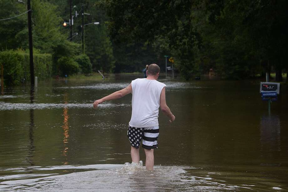 A Bevil Oaks resident makes his way through flooded waters as he and others leave the area following Monday's issuance of a mandatory evacuation. Pine Island Bayou is rising rapidly, and the flooding is expected to exceed 1994's 27 foot flood by at least 4 feet, according to residents.   Photo taken Monday, August 28, 2017 Kim Brent/The Enterprise Photo: Kim Brent / Beaumont Enterprise / BEN