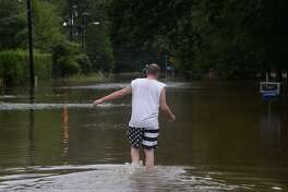 A Bevil Oaks resident makes his way through flooded waters as he and others leave the area following Monday's issuance of a mandatory evacuation. Pine Island Bayou is rising rapidly, and the flooding is expected to exceed 1994's 27 foot flood by at least 4 feet, according to residents. Photo taken Monday, August 28, 2017 Kim Brent/The Enterprise