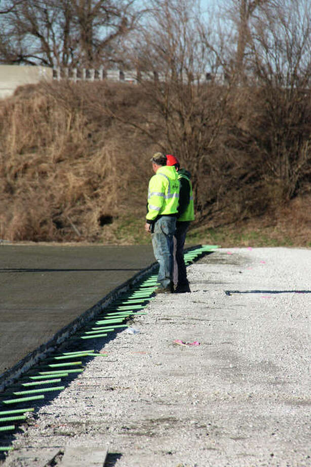 Keller Construction workers confer after checking the latest cement pour on the section of Old Troy Road immediately north of Glen Crossing Road Wednesday. The view is looking north and Interstate 270 is in the background. Photo: Charles Bolinger | The Intelligencer
