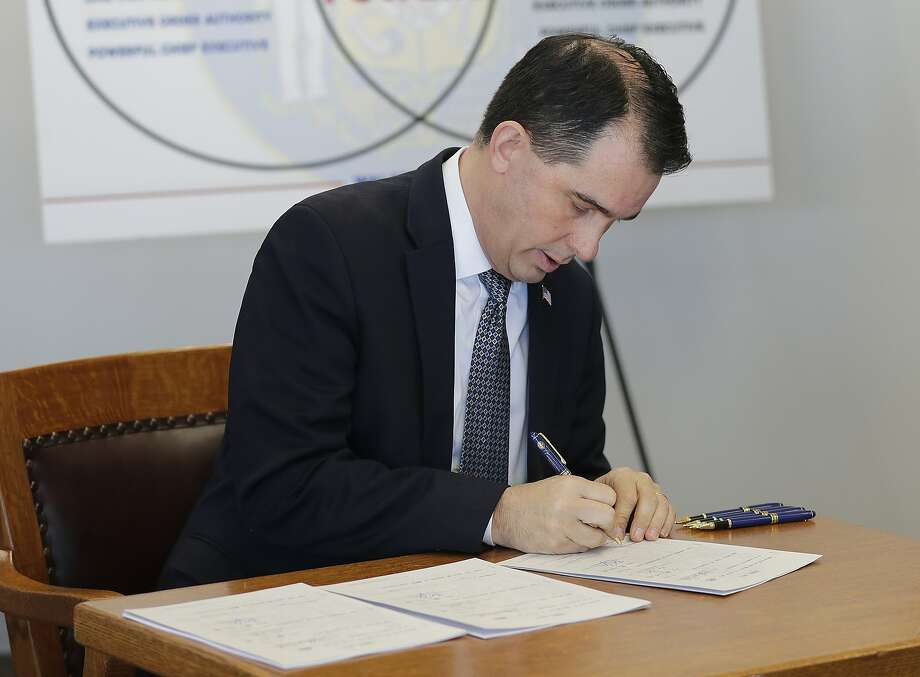 Gov. Scott Walker signs three pieces of legislation during a news conference Friday, Dec. 14, 2018 in Green Bay, Wis. Walker signed a sweeping package of Republican-written legislation Friday that restricts early voting and weakens the incoming Democratic governor and attorney general, brushing aside complaints that he is enabling a brazen power grab and ignoring the will of voters.  (Haley BeMiller/The Post-Crescent via AP) Photo: Haley BeMiller, Associated Press