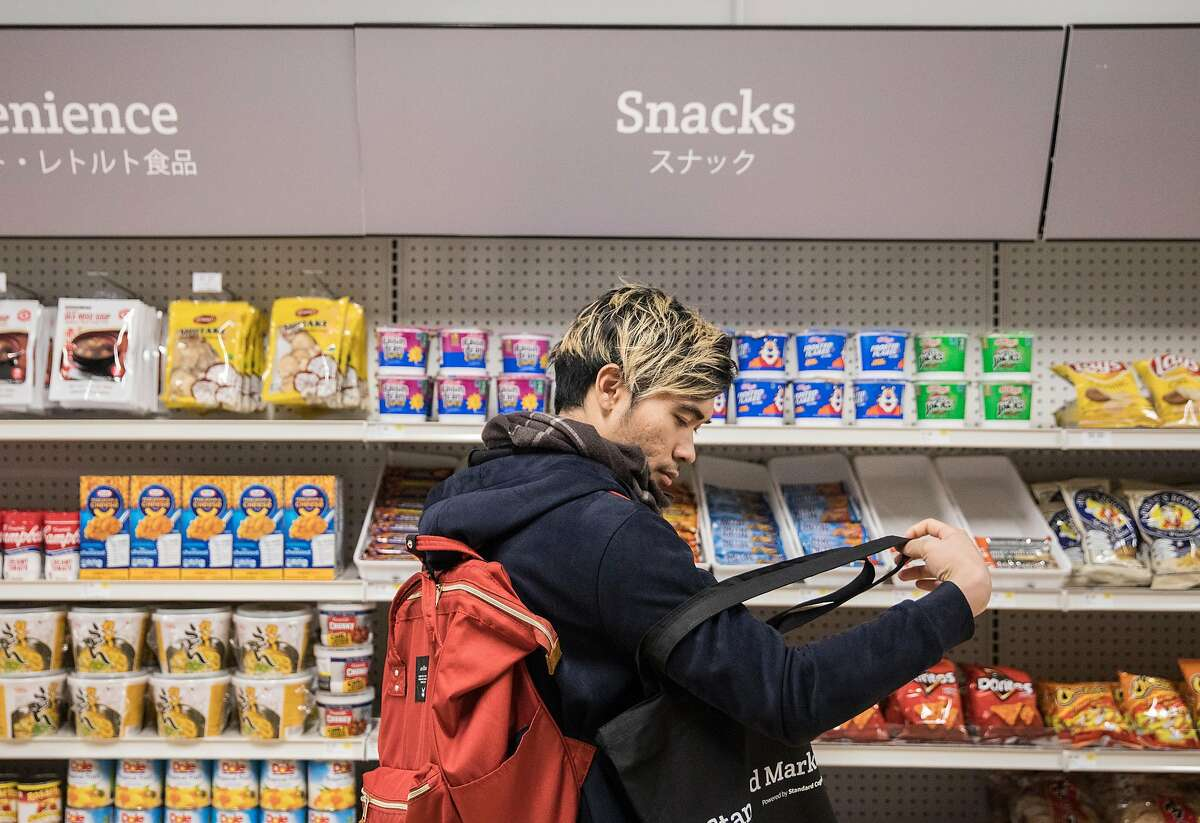 Maytee Chinavanichkit places a bag of chips into his shopping bag at Standard Market, a cashier-less convenience store in San Francisco, Calif. Wednesday, Nov. 28, 2018.