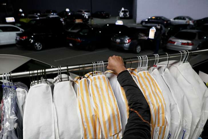 Jamier Scott dropping off cleaned clothes to a driver at Rinse, an on-demand laundry service in San Francisco, Calif., on Thursday, December 13, 2018. Rinse is a startup that provides an on-demand laundry service. The company picks up laundry from clients and delivers it to the warehouse and partners with local laundry services to wash the clothes.
