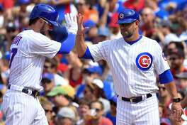 CHICAGO, IL - JULY 22: Chicago Cubs third baseman Kris Bryant (17) celebrates with Chicago Cubs first base coach Brandon Hyde (16) after hitting the ball for a single during the game between the St. Louis Cardinals and the Chicago Cubs on July 22, 2017 at Wrigley Field in Chicago, Illinois. (Photo by Quinn Harris/Icon Sportswire via Getty Images)
