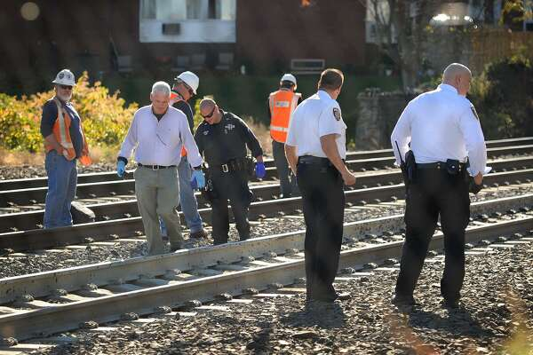 Investigators search the tracks for the remains of a woman killed by an Amtrak train on the southbound track near the Beardsley Avenue crossing in Milford, Conn. on Monday, October 27, 2014.