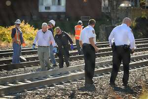 Investigators search the tracks for the remains of a woman killed by an Amtrak train in Milford in 2014.