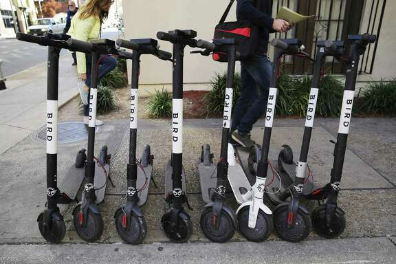 Pedestrians walk past a row of scooters on College Avenue in downtown San Antonio on Dec. 4. A reader complains of scooter clutter.