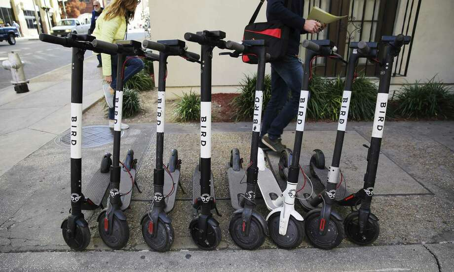Pedestrians walk past a row of scooters on College Avenue in downtown. A reader reflects on a scooter- congested city. Photo: Kin Man Hui / San Antonio Express-News / ©2018 San Antonio Express-News