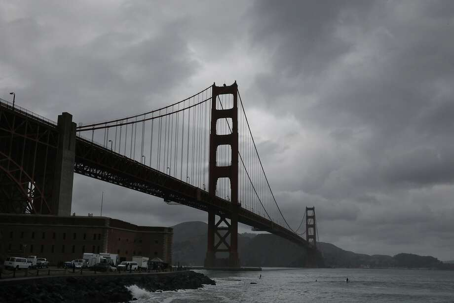 FILE: Storm clouds are seen over the Golden Gate Bridge as surfers surf at Fort Point on Friday, December 14,  2018  in San Francisco, Calif. Photo: Lea Suzuki / The Chronicle