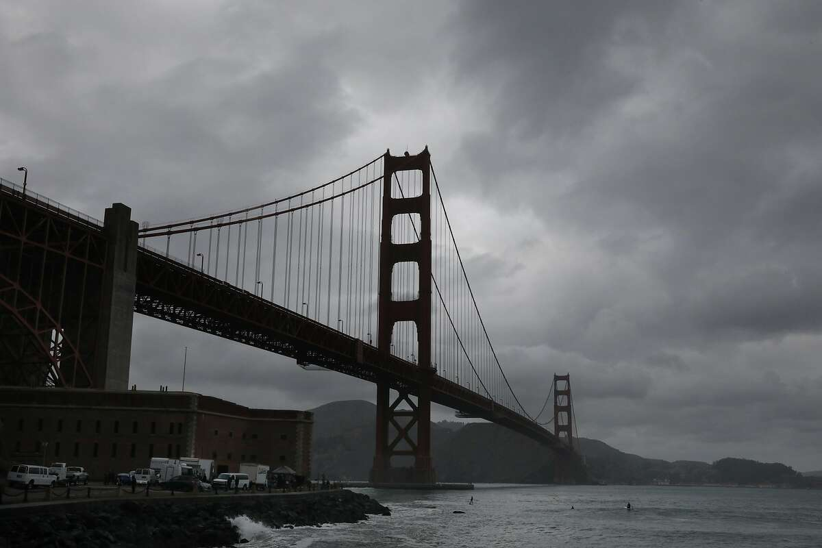 FILE - Storm clouds are seen over the Golden Gate Bridge as surfers surf at Fort Point on Friday, December 14, 2018 in San Francisco, Calif.