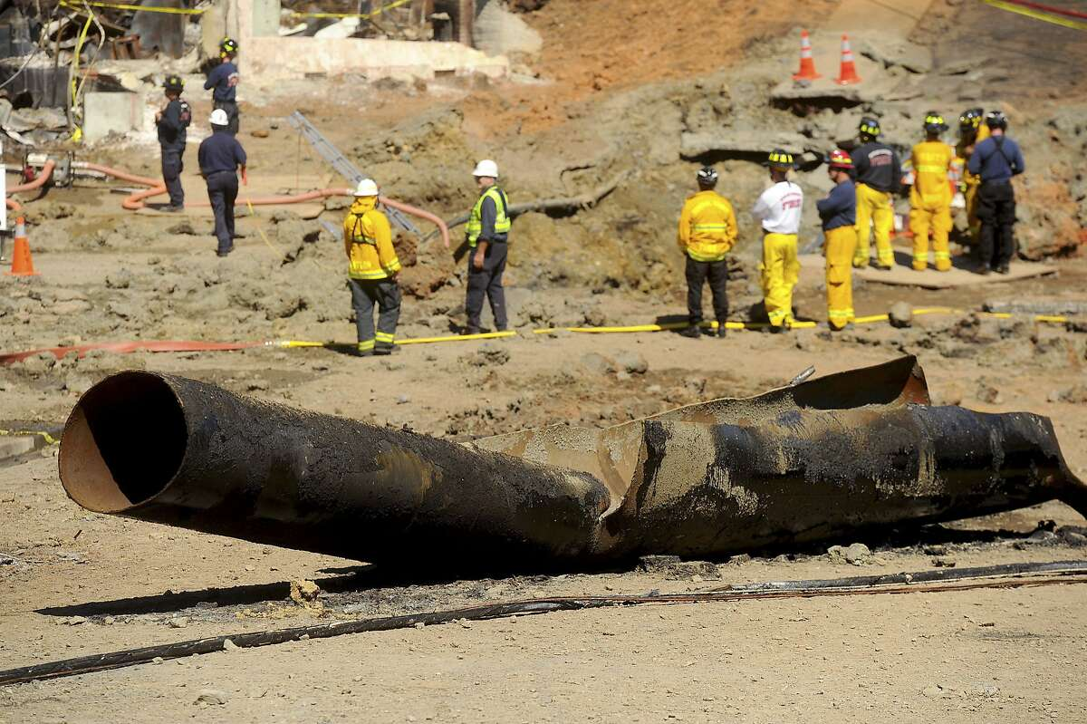 FILE - In this Sept. 11, 2010, file photo, a natural gas line lies broken on a San Bruno, Calif., road after a massive explosion. The California Public Utilities Commission said Friday, Dec. 14, 2018, that an investigation by its staff found Pacific Gas & Electric Co. lacked enough employees to fulfill requests to find and mark natural gas pipelines. A U.S. judge fined the utility $3 million after it was convicted of six felony charges for failing to properly maintain a natural gas pipeline that exploded south of San Francisco in 2010, killing eight people. (AP Photo/Noah Berger, File)