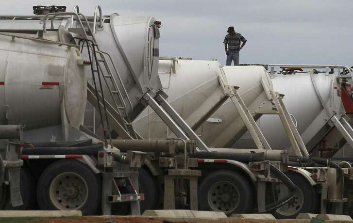 A man works on top of a row of tanker trucks at a gas station in Cotulla, Texas, in 2014. Oil and gas transportation company Product & Logistics Services is laying off 188 workers at its Pleasanton and Von Ormy sites.