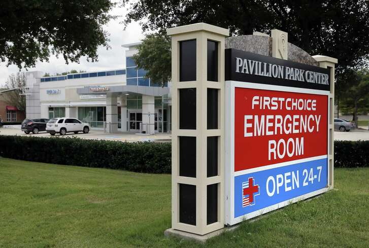 A sign by a nearby road intersection advertises a First Choice Emergency Room, rear, Thursday, Aug. 18, 2016, in Richardson, Texas. Freestanding emergency centers have sprouted in recent years across the suburban landscape, taking root in affluent neighborhoods and directly challenging nearby medical clinics and hospitals.