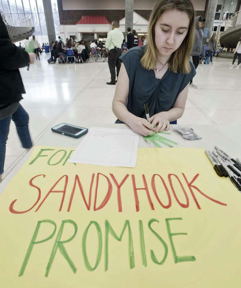 Elizabeth Casolo, a sophomore, writes a kindness note at the Roots and Shoots table in the student center at Greenwich High School, for the anniversary of the Sandy Hook shooting. Friday, Dec. 14, 2018 Photo: Scott Mullin / For Hearst Connecticut Media / The News-Times Freelance