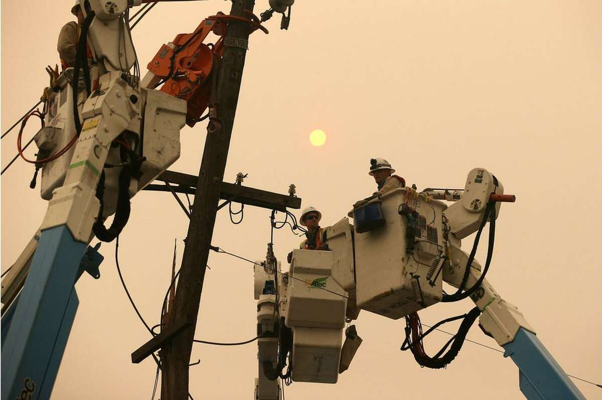 In this Nov. 9, 2018 file photo, Pacific Gas & Electric crews work to restore power lines in Paradise, Calif. PG&E said in a new filing with the state that it determined weather conditions were no longer dangerous enough to warrant a massive power shut off on Nov. 8 - a decision that came as a massive fire was tearing through a Northern California town. (AP Photo/Rich Pedroncelli, File)