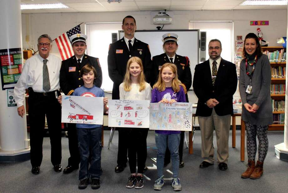Each year, students at Lake Garda Elementary and Harwinton Consolidated School participate in Fire Prevention Week (FPW). Above, at Harwinton Consolidated School, are Alan Beitman, Superintendent; Seth Kellogg, Captain, Harwinton Westside Fire Department; Kevin Ferrarotti, Fire Prevention Officer; Bill Rinko, Past Deputy Chief; Mike Criss, Harwinton First Selectman; Caroline Luke, Art teacher. Front row: Jeremiah Rowland, 3rd place; Amelia Eggleston, 2nd place; Caroline Hayes, 1st place. Photo: Stephanie Cowger / Contributed Photo /
