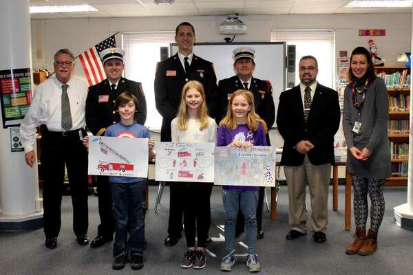Each year, students at Lake Garda Elementary and Harwinton Consolidated School participate in Fire Prevention Week (FPW). Above, at Harwinton Consolidated School, are Alan Beitman, Superintendent; Seth Kellogg, Captain, Harwinton Westside Fire Department; Kevin Ferrarotti, Fire Prevention Officer; Bill Rinko, Past Deputy Chief; Mike Criss, Harwinton First Selectman; Caroline Luke, Art teacher. Front row: Jeremiah Rowland, 3rd place; Amelia Eggleston, 2nd place; Caroline Hayes, 1st place.