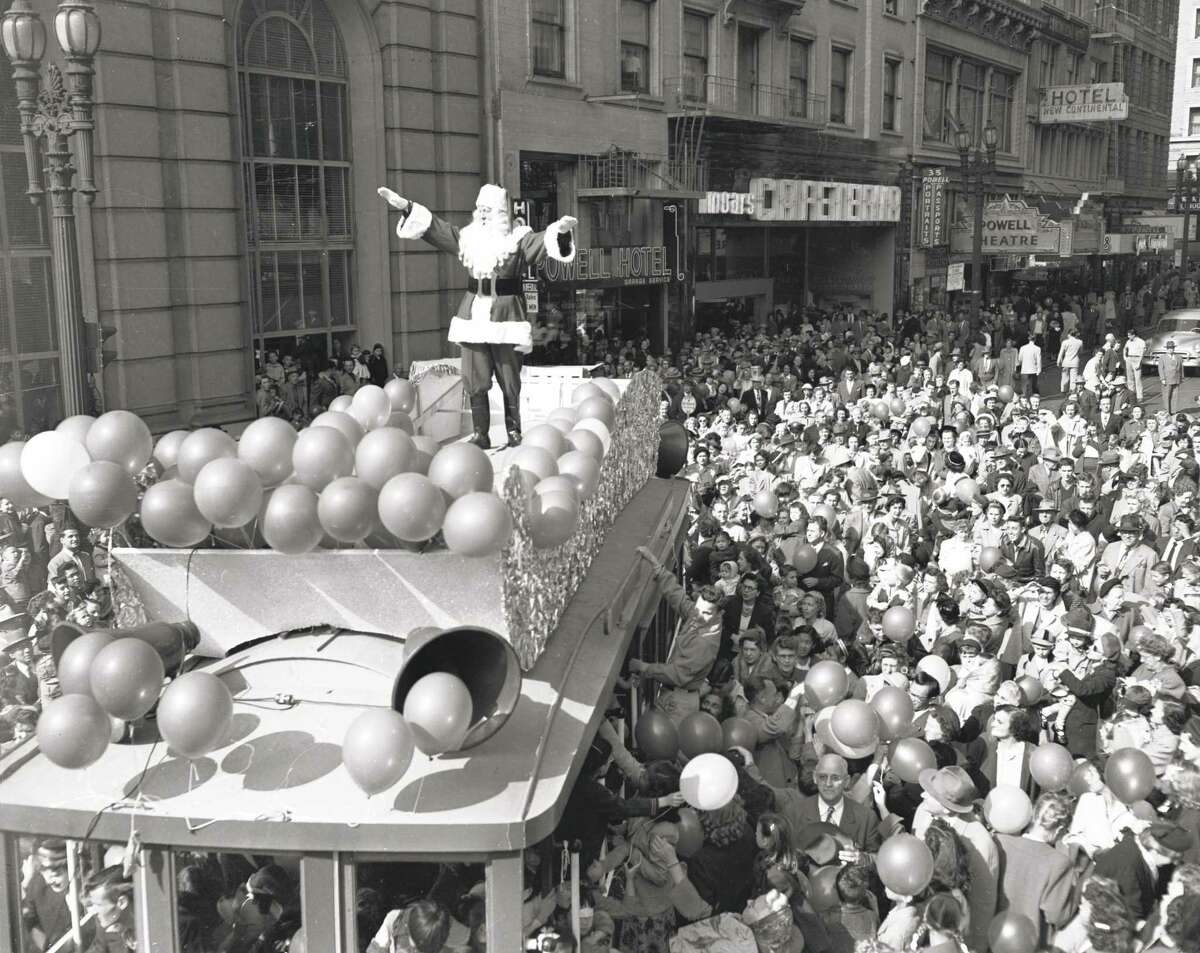 The Emporium's Santa Claus, surrounded by thousands of children, arrives in November 1951 at Powell and Market streets in a sleigh on top of a cable car.
