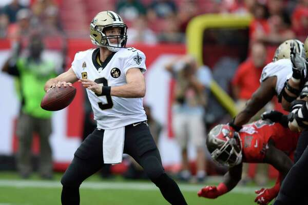 FILE - In this Sunday, Dec. 9, 2018 file photo, New Orleans Saints quarterback Drew Brees (9) throws a pass against the Tampa Bay Buccaneers during the first half of an NFL football game in Tampa, Fla. When Drew Brees became the NFL's all-time leader in yards passing, he wanted to come up with some sort of gift to thank those who coached him, caught the 6,357 completions it took to set the record, and those who blocked while he threw. His solution was an exhaustive process than involved the production of about 175 unique commemorative footballs and the enlisting Saints front office and public relations staff to help track down 99 receivers, 56 offensive linemen, 11 head or assistant coaches from his 18 pro seasons, as well as a few others Brees saw as instrumental in his success.