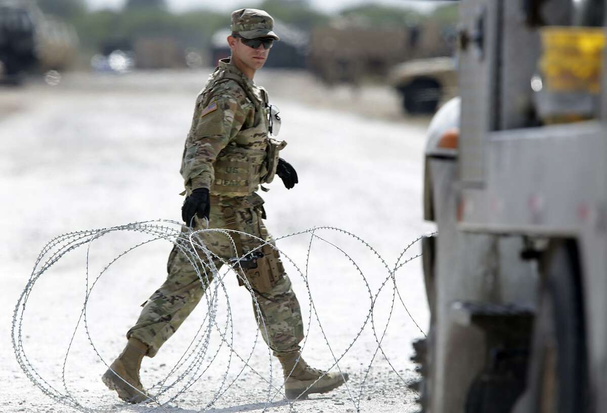A member of the Military Police opens a razon wire gate for a military vehicle to enter a camp next to the Donna-Rio Bravo International Bridge, on Tuesday, Dec. 4, 2018.