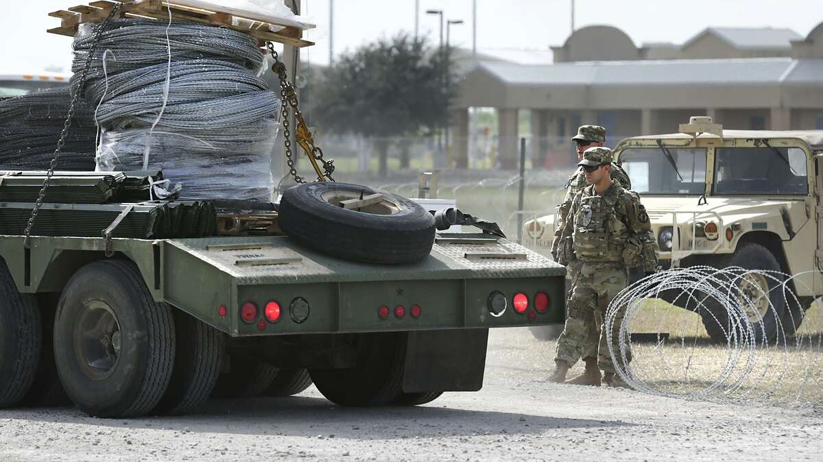 Military personel hold open a razor wire gate to let in a shipment of more wire at the military camp next to the Donna-Rio Bravo International Bridge, on Tuesday, Dec. 4, 2018.