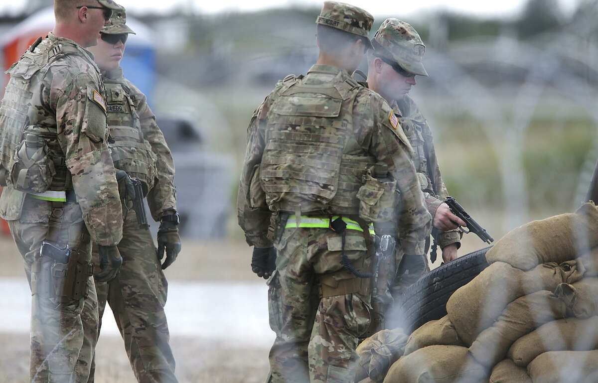 Military personel perform a safety measure with their side arms called chamber clearing at the military camp next to the Donna-Rio Bravo International Bridge, on Tuesday, Dec. 4, 2018.