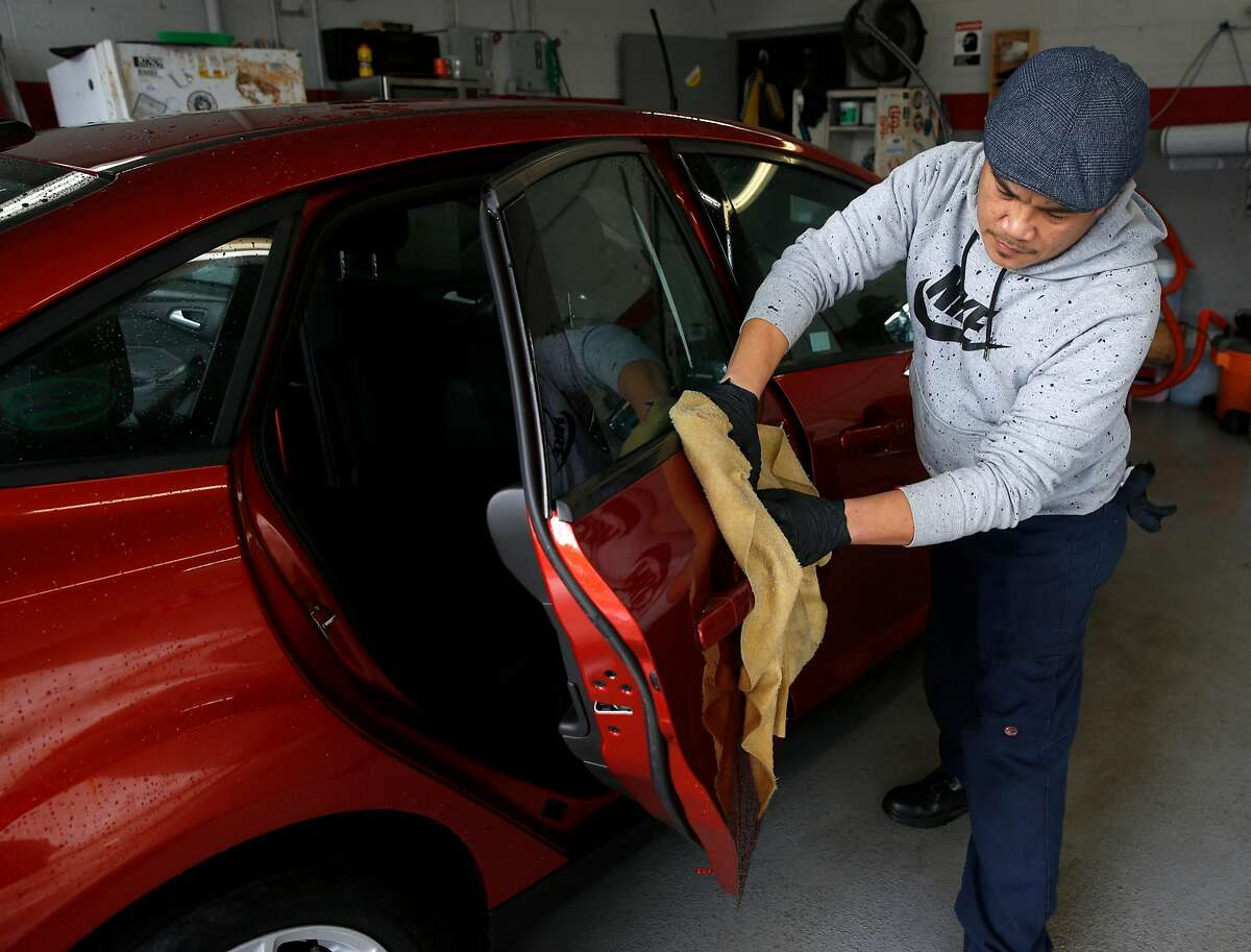 Edmon Aguiluz details a new car for delivery to a customer at the Serramonte Ford dealership in Colma, Calif. on Friday, Dec. 14, 2018. Beginning Jan. 1 auto dealerships will be required to affix temporary license plates to every vehicle sold and before it drives off the lot.