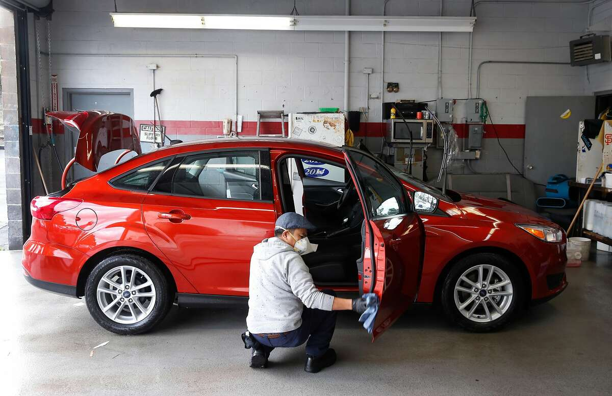 Edmon Aguiluz preps a new car for delivery to a customer at the Serramonte Ford dealership in Colma, Calif. on Friday, Dec. 14, 2018. Beginning Jan. 1 auto dealerships will be required to affix temporary license plates to every vehicle sold and before it drives off the lot.