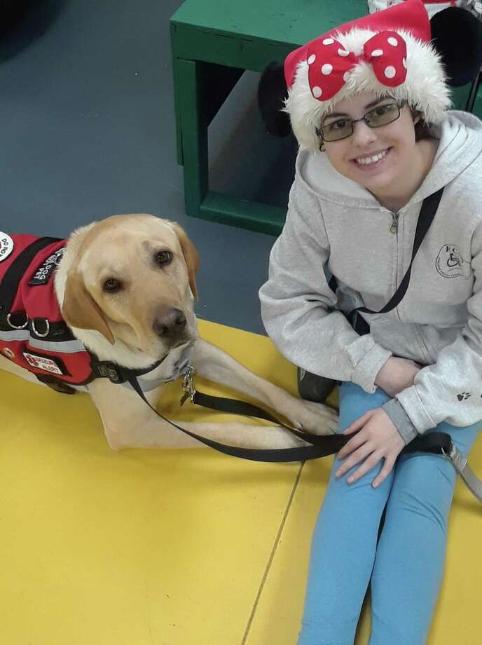 ECAD in Winchester held a holiday party for staff, volunteers and clients on Friday. Among the guests was Cassidy Schott, 21, of Southbury, with her dog Sonoma. Schott, who has been living with severe Lyme disease since the age of 12, is prone to seizures. Sonoma recognizes the symptoms and helps the young woman whenever they occur by alerting others. Photo: Emily M. Olson / Hearst Connecticut Media /