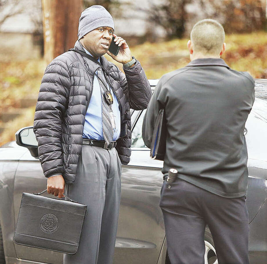 Members of the Illinois State Police Violent Crime Unit, which is handling the investigation, confer at the scene Friday morning. Police were on the scene for about six hours processing evidence and talking to neighbors. Photo: John Badman | The Telegraph