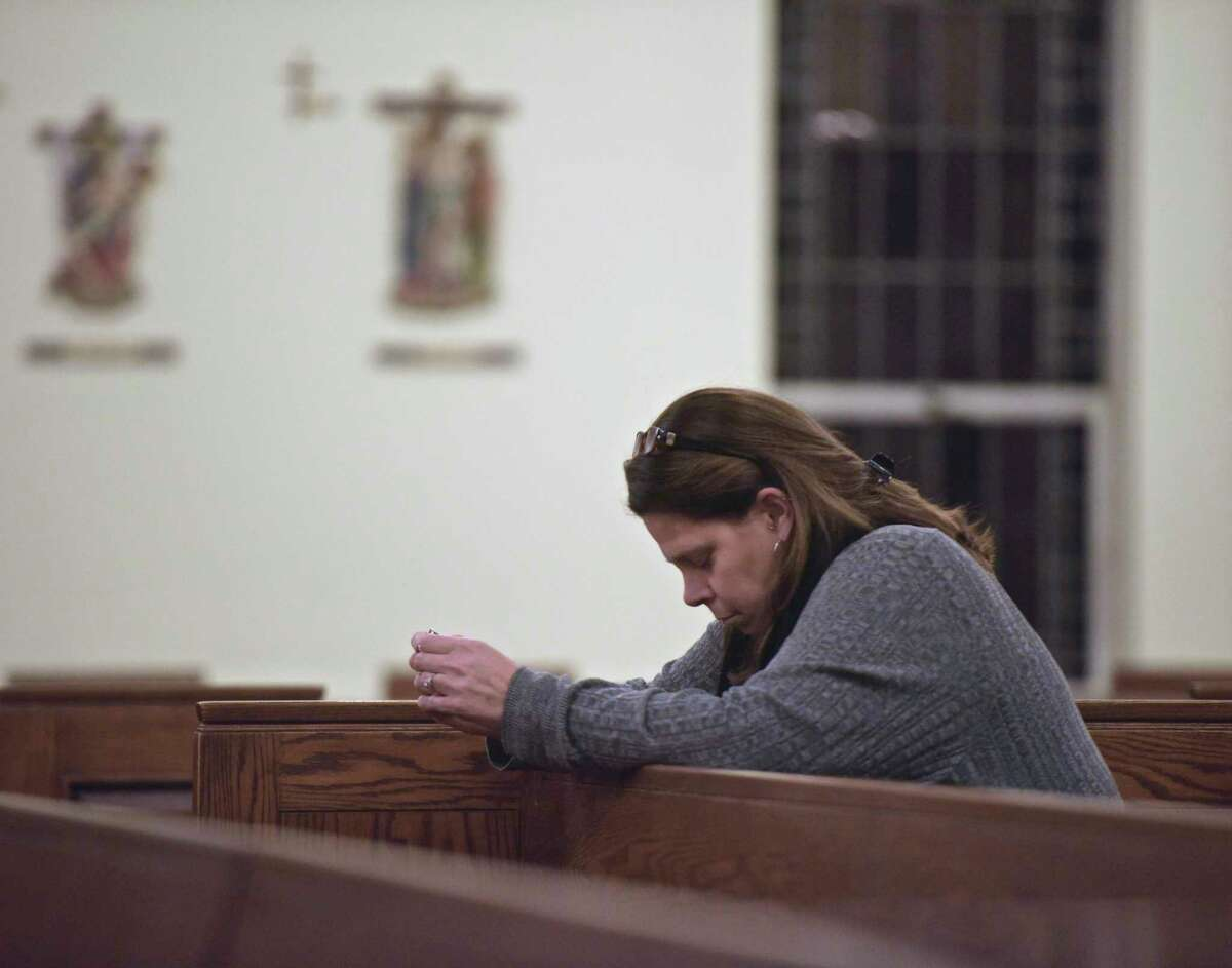 Pam Carlson, of Newtown, prays before a remembrance mass on the 6th anniversary of the Sandy Hook shootings at St. Rose of Lima Church, in Newtown, Conn, December 14, 2018.