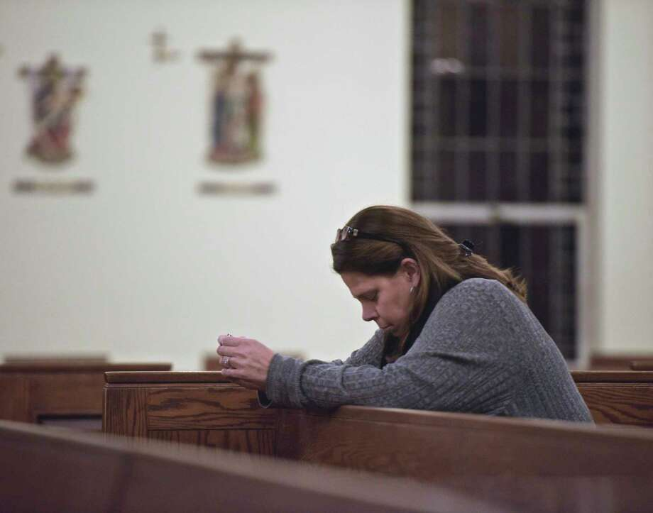 Pam Carlson, of Newtown, prays before a remembrance mass on the 6th anniversary of the Sandy Hook shootings at St. Rose of Lima Church, in Newtown, Conn, December 14, 2018. Photo: H John Voorhees III, Hearst Connecticut Media / The News-Times