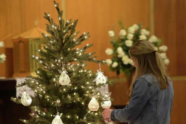 A member of the St Rose Youth Group hangs one of 26 glass angel's on a tree during the remembrance mass on the 6th anniversary of the Sandy Hook shootings at St. Rose of Lima Church, in Newtown, Conn, December 14, 2018.