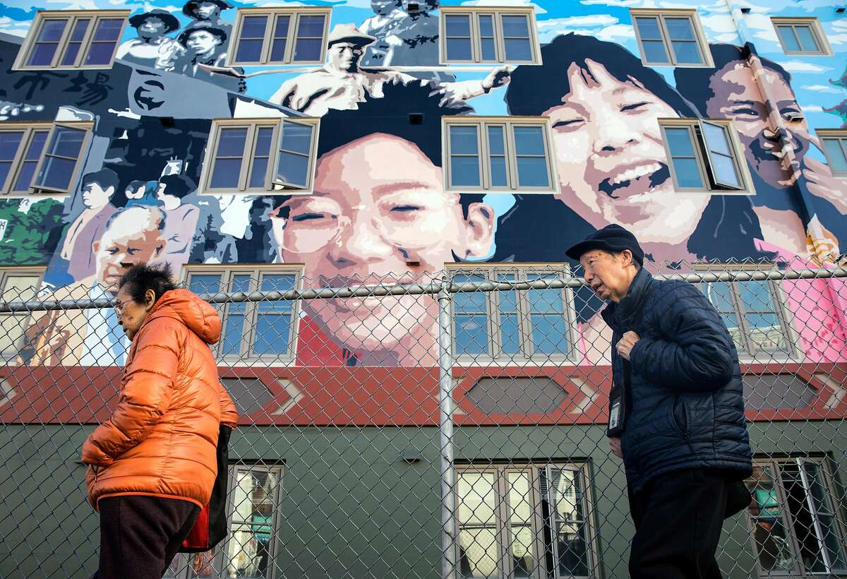 Pedestrians walk past a large mural painted on the side of the Ping Yuen housing project in the Chinatown neighborhood of San Francisco, Calif. Thursday, Nov. 8, 2018.