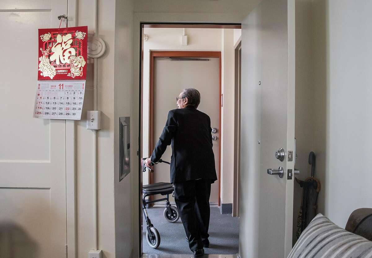 Chang Jok Lee, 92, exits her newly-renovated apartment to walk around the main courtyard at Ping Yuen Center in the Chinatown neighborhood of San Francisco, Calif. Thursday, Nov. 8, 2018.