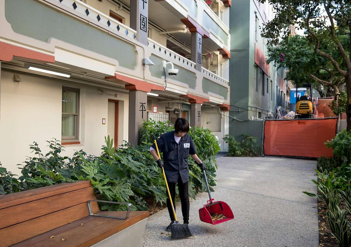 A janitor sweeps the main entryway of Ping Yuen Center in the Chinatown neighborhood of San Francisco, Calif. Thursday, Nov. 8, 2018.