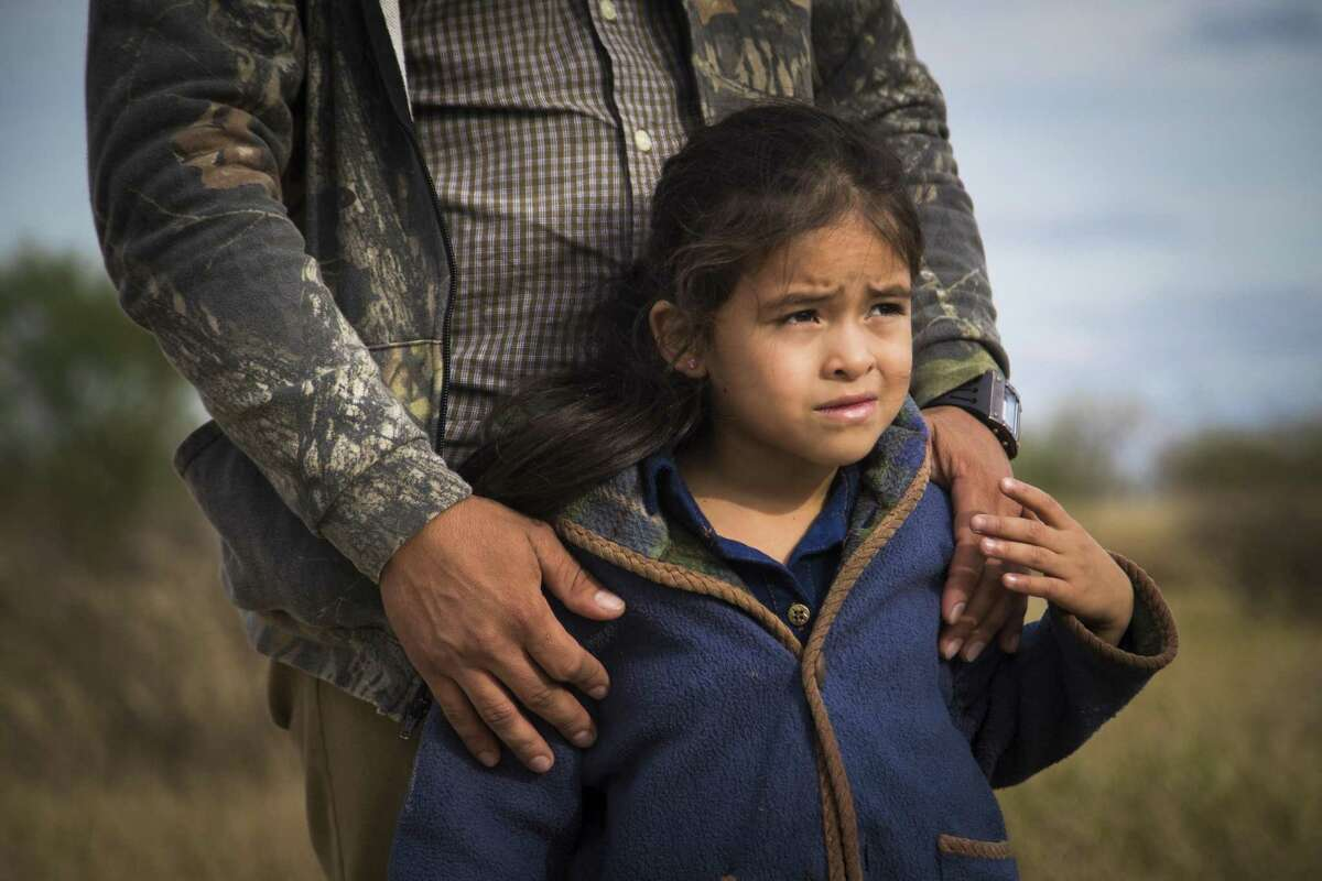 Nataly Diaz, 6, holds her father's hand after crossing the Rio Grande River and waits for Border Patrol agents to finish processing them, Tuesday, Dec. 11, 2018, in Peñitas.