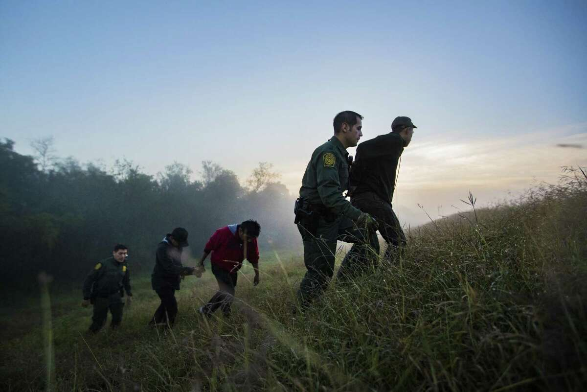 Five young men are detained by Border Patrol agents near the Rio Grande River on Thursday, Dec. 13, 2018, in Mission. The group tried to escape after they were intercepted hiding in the bushes.