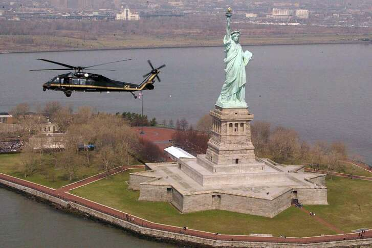A Black Hawk helicopter from the Department of Homeland Security's Bureau of Immigration and Customs Enforcement passes by the Statute of Liberty in New York Harbor.