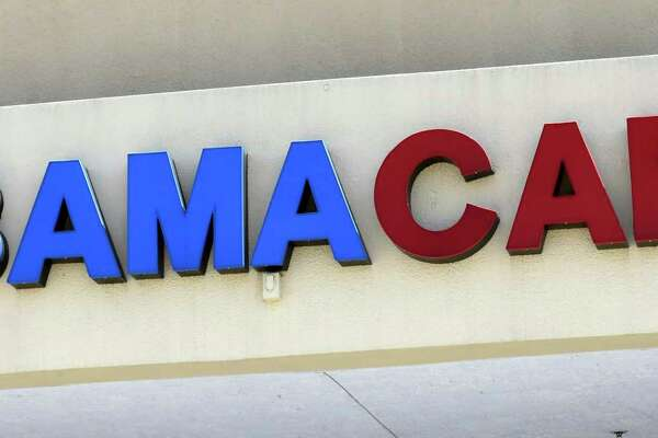 """File- This May 11, 2017, file photo shows an Obamacare sign being displayed on the storefront of an insurance agency in Hialeah, Fla. A conservative federal judge in Texas on Friday, Dec. 14, 2018, ruled the Affordable Care Act """"invalid"""" on the eve of the sign-up deadline for next year. But with appeals certain, even the Trump White House said the law will remain in place for now. In a 55-page opinion, U.S. District Judge Reed O'Connor ruled Friday that last year's tax cut bill knocked the constitutional foundation from under """"Obamacare"""" by eliminating a penalty for not having coverage. The rest of the law cannot be separated from that provision and is therefore invalid, he wrote."""