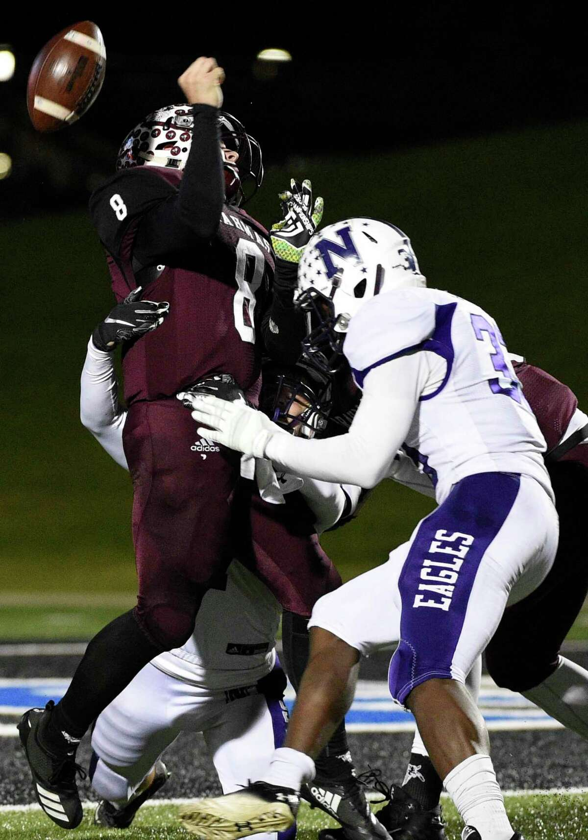 East Bernard quarterback Hunter Goudeau (8) fumbles after being sacked by Newton linebacker Jadrian McGraw, right, on the last play of the game during the second half of a 3A State semi-final high school football playoff game, Friday, Dec. 14, 2018, in New Caney, TX. Newton won the game 21-14.