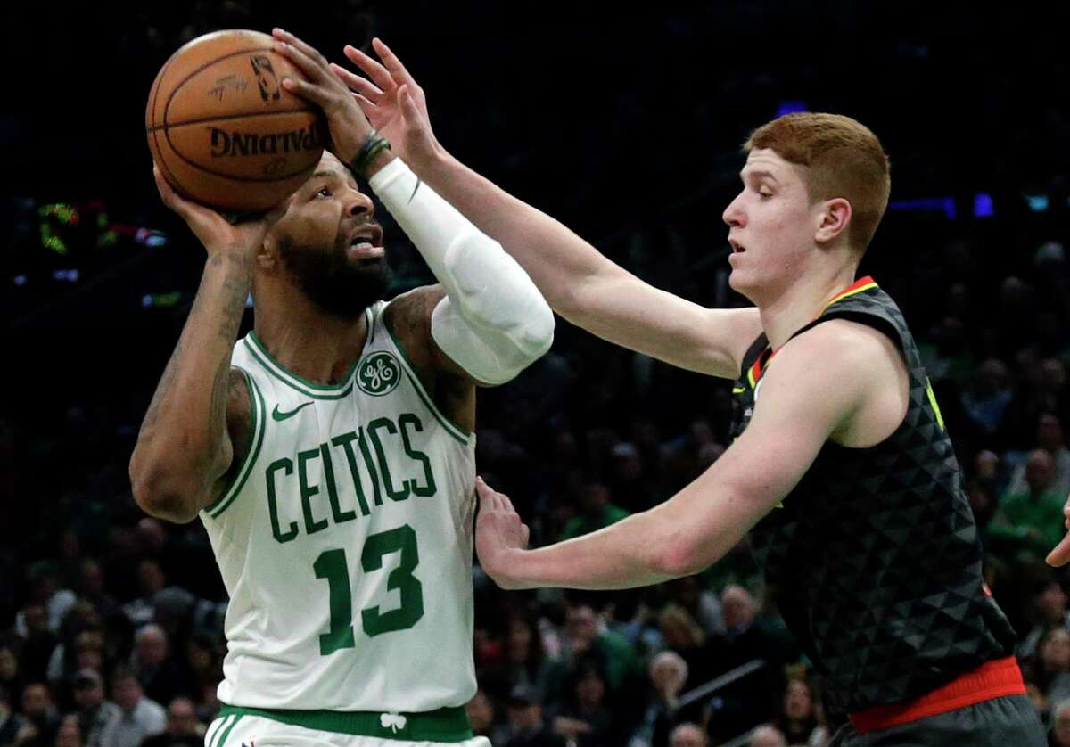 Boston Celtics forward Marcus Morris (13) goes up to shoot against Atlanta Hawks guard Kevin Huerter in the second quarter of an NBA basketball game, Friday, Dec. 14, 2018, in Boston. (AP Photo/Elise Amendola)