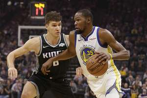 Golden State Warriors forward Kevin Durant, right, drives to the basket against Sacramento Kings guard Bogdan Bogdanovic 2during the first half of an NBA basketball game Friday, Dec. 14, 2018, in Sacramento, Calif. (AP Photo/Rich Pedroncelli)
