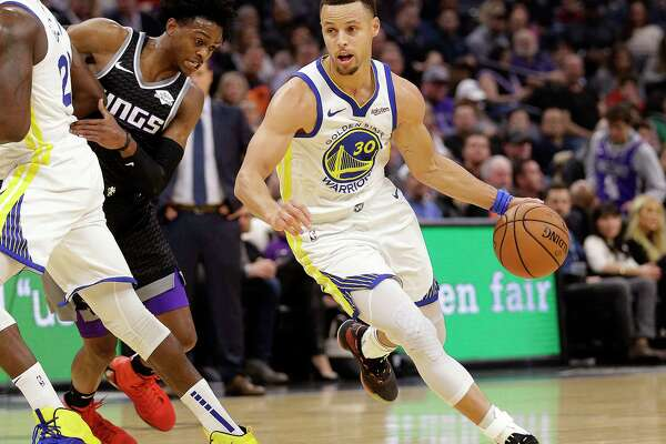 Sacramento Kings guard De'Aaron Fox, left, tries to fight through a screen as he guards against Golden State Warriors guard Stephen Curry, right, during the first half of an NBA basketball game Friday, Dec. 14, 2018, in Sacramento, Calif.