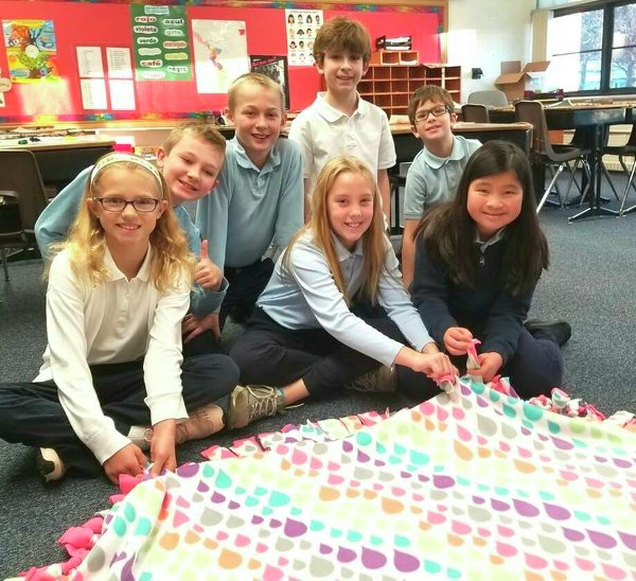 Blessed Sacrament Elementary fifth-grade students, front, from left, Karis Galus, Emerson Boothe and Molly Stemple, and back, from left, Gibby Davis, Matthew Berg, Sam Schroden and Kyle Gavin pose with the prayer tie-blanket they helped finish for a former Blessed Sacrament student who is battling cancer. (Photo provided/Patrick Bevier)